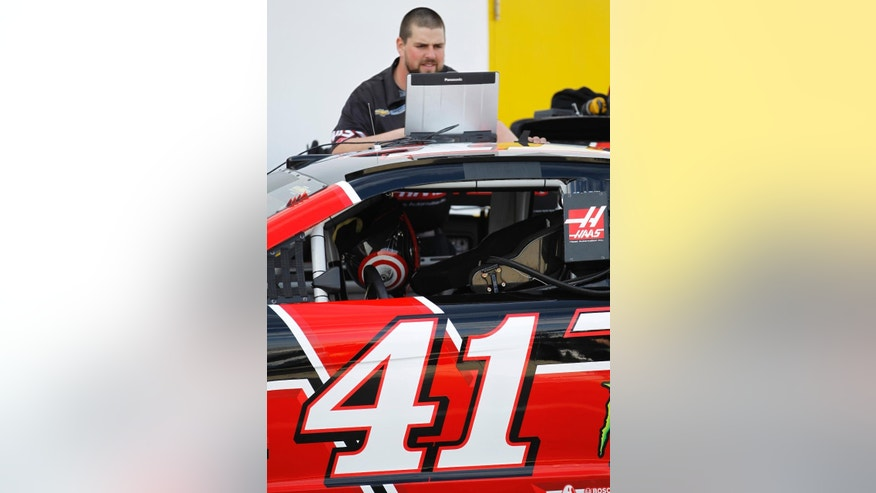 A piece of tape covers the name over the driver's window as a crew member works on Kurt Busch's car before practice for the Daytona 500 NASCAR Sprint Cup series auto race at Daytona International Speedway in Daytona Beach, Fla., Saturday, Feb. 21, 2015. Driver Regan Smith will fill in for Busch in the wake of Busch's suspension on Friday. (AP Photo/Terry Renna)