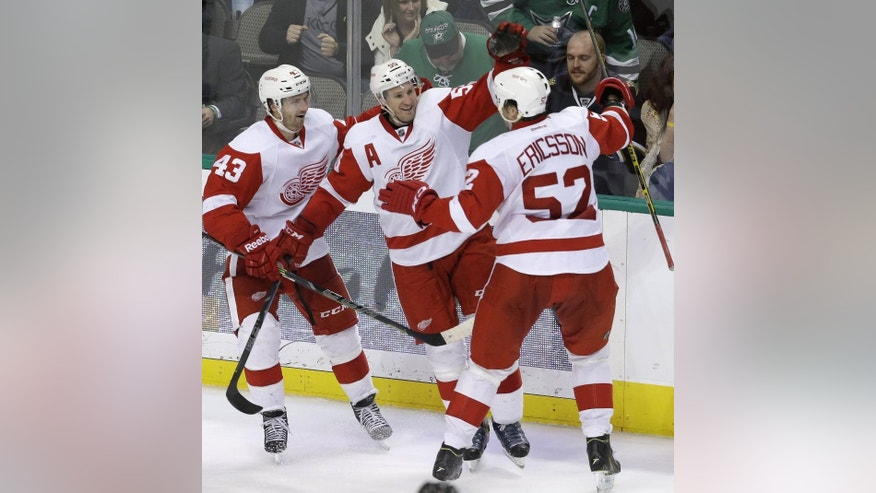 Detroit Red Wings defenseman Niklas Kronwall (55) celebrates after scoring the winning goal with teammates Darren Helm (43) and Jonathan Ericsson (52) during overtime in an NHL hockey game against the Dallas Stars, Saturday, Feb. 21, 2015, in Dallas. The Red Wings won 7-6. (AP Photo/LM Otero)