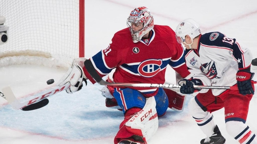Montreal Canadiens goaltender Carey Price makes a save on Columbus Blue Jackets' Cam Atkinson during the second period of an NHL hockey game, Saturday, Feb. 21, 2015 in Montreal. (AP Photo/Canadian Press, Graham Hughes)
