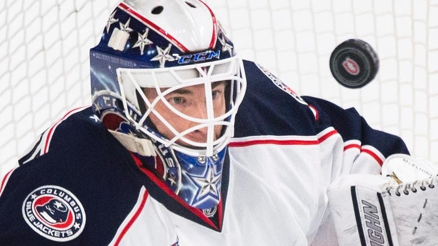 Columbus Blue Jackets goaltender Curtis McElhinney keeps his eyes on the puck as he makes a save on the Montreal Canadiens during the first period of an NHL hockey game, Saturday, Feb. 21, 2015 in Montreal. (AP Photo/Canadian Press, Graham Hughes)