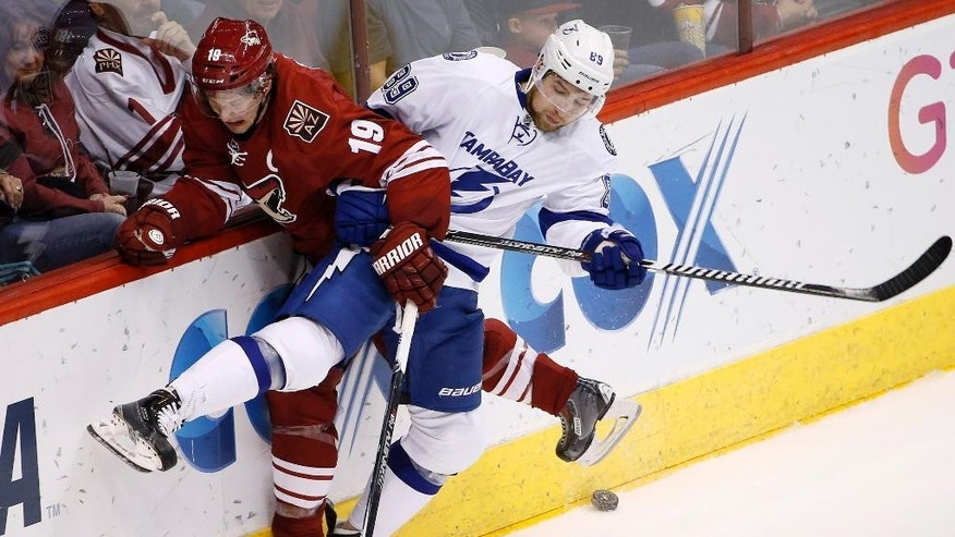 Arizona Coyotes' Shane Doan (19) and Tampa Bay Lightning's Nikita Nesterov (89), of Russia, collide against the boards during the second period of an NHL hockey game Saturday, Feb. 21, 2015, in Glendale, Ariz. (AP Photo/Ross D. Franklin)