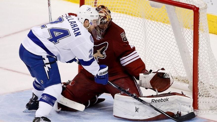 Arizona Coyotes' Mike Smith, right, makes a save on a shot by Tampa Bay Lightning's Ryan Callahan, left, during the second period of an NHL hockey game Saturday, Feb. 21, 2015, in Glendale, Ariz. (AP Photo/Ross D. Franklin)