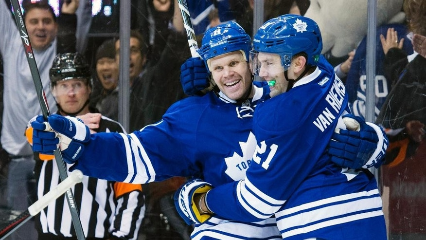 Toronto Maple Leafs' Olli Jokinen, front left, and James van Riemsdyk celebrate their overtime win in NHL hockey game action against the Winnipeg Jets in Toront, Saturday, Feb. 21, 2015. (AP Photo/The Canadian Press, Darren Calabrese)