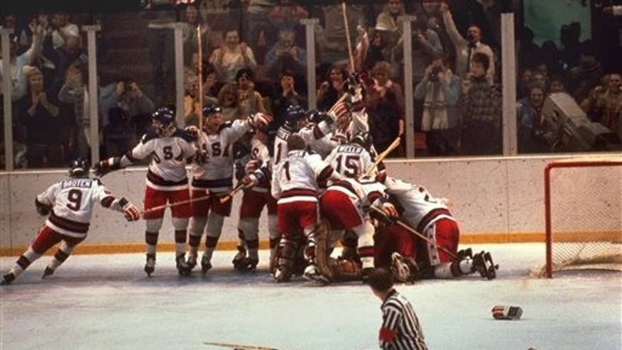 FILE -In this Feb. 22, 1980, file photo, the U.S. hockey team pounces on goalie Jim Craig after a 4-3 victory against the Soviets in the 1980 Olympics, as a flag waves from the Lake Placid, N.Y., crowd. (AP Photo, File)
