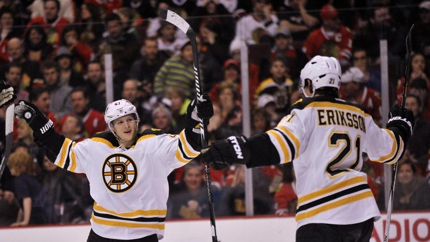 Boston Bruins' Tony Krug (47), celebrates with teammate Loui Eriksson (21), after Eriksson scored a goal during the first period of an NHL hockey game against the Chicago Blackhawks in Chicago, Sunday, Feb. 22, 2015. (AP Photo/Paul Beaty)