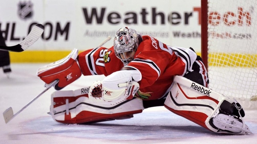 Chicago Blackhawks goalie Corey Crawford (50), makes a save during the first period of an NHL hockey game against the Boston Bruins in Chicago, Sunday, Feb. 22, 2015. (AP Photo/Paul Beaty)