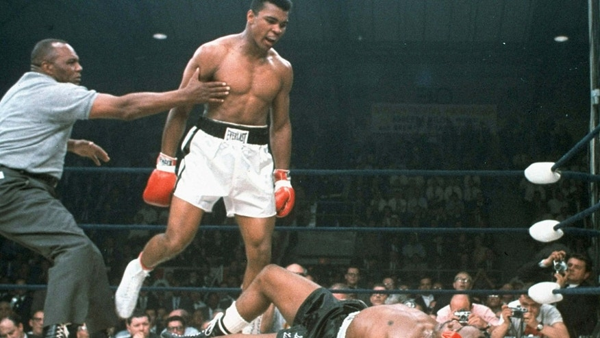 May 25, 1965: Heavyweight champion Muhammad Ali is held back by referee Joe Walcott after Ali dropped challenger Sonny Liston less than two minutes into the first round of their heavyweight title fight.