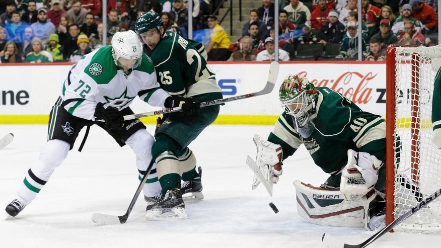 Minnesota Wild goalie Devan Dubnyk (40) deflects a shot as Wild defenseman Jonas Brodin (25) holds back Dallas Stars right wing Erik Cole (72) during the second period of an NHL hockey game in St. Paul, Minn., Sunday, Feb. 22, 2015. (AP Photo/Ann Heisenfelt)