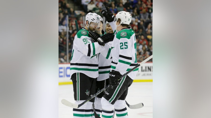 Dallas Stars center Jason Spezza (90) is congratulated by teammates  Trevor Daley and Brett Ritchie (25) after scoring on Minnesota Wild goalie Devan Dubnyk during the second period of an NHL hockey game in St. Paul, Minn., Sunday, Feb. 22, 2015. (AP Photo/Ann Heisenfelt)