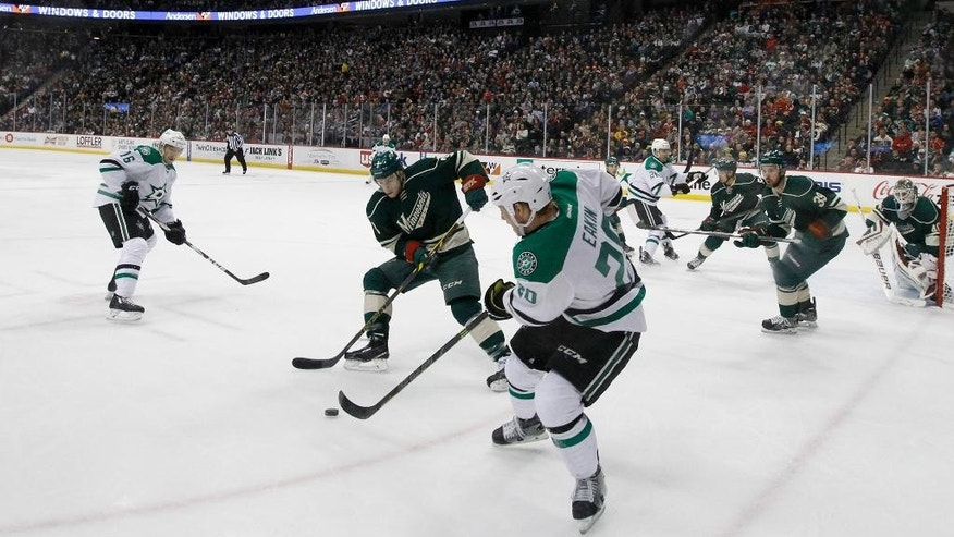 Dallas Stars center Cody Eakin (20) passes the puck past Minnesota Wild center Charlie Coyle (3) during the second period of an NHL hockey game in St. Paul, Minn., Sunday, Feb. 22, 2015. (AP Photo/Ann Heisenfelt)