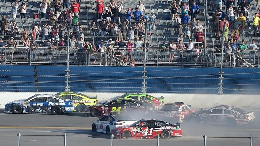 Ricky Stenhouse Jr. (17), Paul Menard (27), Jeff Gordon (24), Matt Crafton (18), Trevor Bayne (6), Regan Smith (41), AJ Allmendinger (47) and Reed Sorenson (44) collide in the back stretch on the final lap of the Daytona 500 NASCAR Sprint Cup series auto race at Daytona International Speedway, Sunday, Feb. 22, 2015, in Daytona Beach, Fla.(AP Photo/Phelan M. Ebenhack)