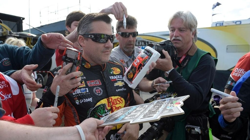 Tony Stewart, center, signs autographs before practice for the Daytona 500 NASCAR Sprint Cup series auto race at Daytona International Speedway in Daytona Beach, Fla., Saturday, Feb. 21, 2015. (AP Photo/Phelan M. Ebenhack)