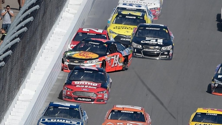 Tony Stewart (14) hits the wall with Ryan Blaney (21) on the front stretch during the Daytona 500 NASCAR Sprint Cup series auto race at Daytona International Speedway, Sunday, Feb. 22, 2015, in Daytona Beach, Fla. (AP Photo/Phelan M. Ebenhack)