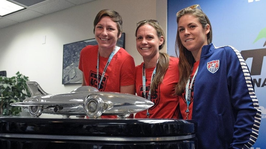 Members of the U.S. Women's National Soccer team, from left, Abby Wambach, Christie Rampone, and Kelley O'Hara, pose with the winner's trophy during a news conference before the Daytona 500 NASCAR Sprint Cup series auto race at Daytona International Speedway in Daytona Beach, Fla., Sunday, Feb. 22, 2015. The women are the honorary starters for the race. (AP Photo/Phelan M. Ebenhack)