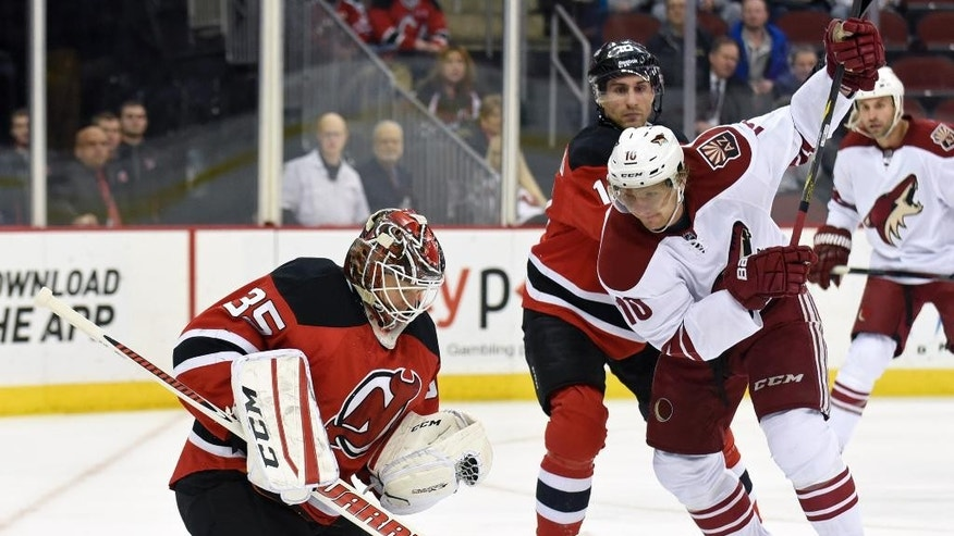 New Jersey Devils goaltender Cory Schneider, left,  gloves the puck as Devils' Peter Harrold checks Arizona Coyotes' Martin Erat, right, during the first period of an NHL hockey game Monday, Feb. 23, 2015, in Newark, N.J. (AP Photo/Bill Kostroun)
