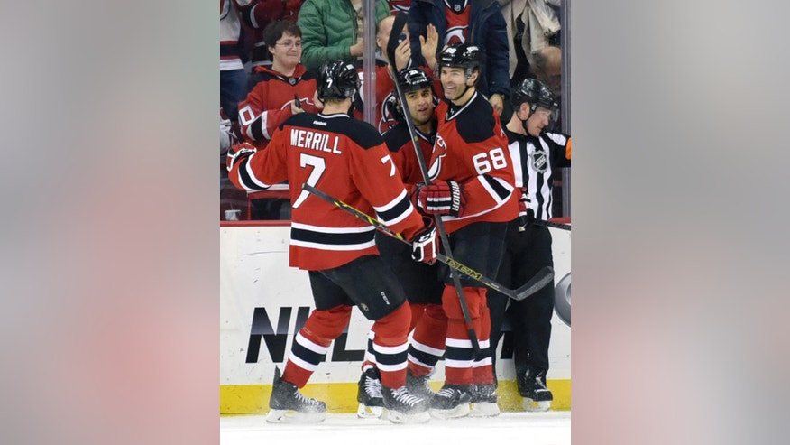 New Jersey Devils' Scott Gomez celebrates his goal with Jon Merrill (7) and Jaromir Jagr, right, during the first period of an NHL hockey game Monday, Feb. 23, 2015, in Newark, N.J. (AP Photo/Bill Kostroun)