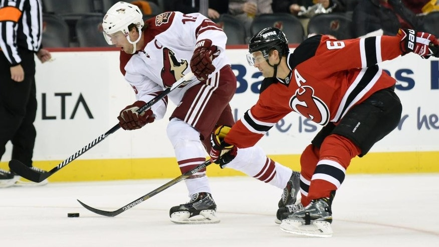 Arizona Coyotes' Shane Doan, left, skates with the puck as New Jersey Devils' Andy Greene attempts a poke check during the first period of an NHL hockey game Monday, Feb. 23, 2015, in Newark, N.J. (AP Photo/Bill Kostroun)