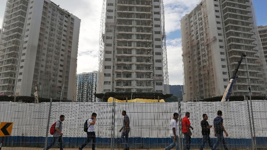 People walk past the 2016 Olympic Games's Athletes Village under construction in Rio de Janeiro, Brazil, Thursday, Feb. 19, 2015. International Olympic Committee inspectors will start a tour of facilities next week. (AP Photo/Leo Correa)