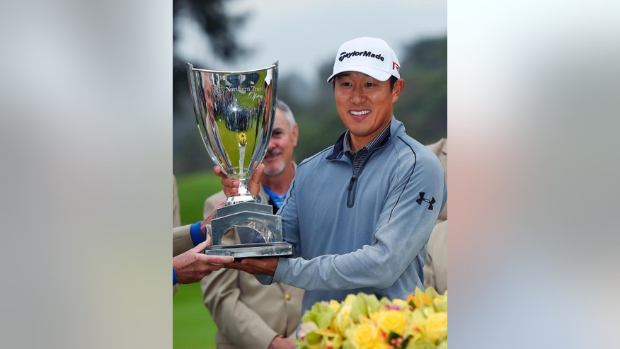 James Hahn holds the winner's trophy after his one-stroke victory on the third playoff hole against two other players in the final round of the Northern Trust Open golf tournament at Riviera Country Club in the Pacific Palisades area of Los Angeles Sunday, Feb. 22, 2015.(AP Photo/Mark J. Terrill)