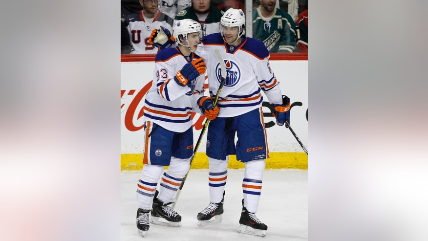 Edmonton Oilers left wing Benoit Pouliot (67) celebrates with teammate Ryan Nugent-Hopkins (93) after Pouliot scored on Minnesota Wild goalie Devan Dubnyk during the first period of an NHL hockey game in St. Paul, Minn., Tuesday, Feb. 24, 2015. (AP Photo/Ann Heisenfelt)
