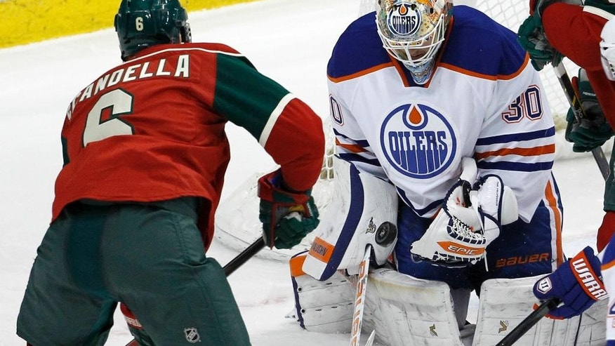 Edmonton Oilers goalie Ben Scrivens (30) stops a shot by Minnesota Wild defenseman Marco Scandella (6) during the third period of an NHL hockey game in St. Paul, Minn., Tuesday, Feb. 24, 2015. The Oilers won 2-1. (AP Photo/Ann Heisenfelt)