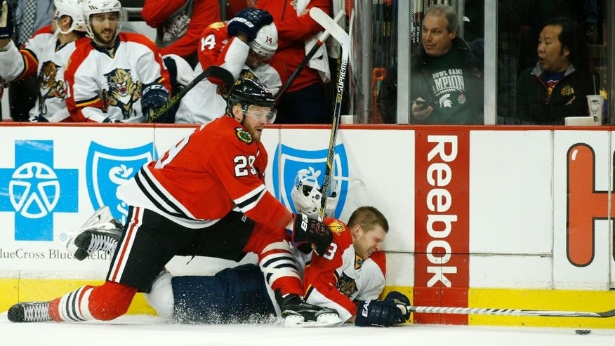 Florida Panthers defenseman Steven Kampfer (3) has his helmet knocked off as he collides with Chicago Blackhawks left wing Bryan Bickell (29) during the first period of an NHL hockey game on Tuesday, Feb. 24, 2015, in Chicago. (AP Photo/Andrew A. Nelles)