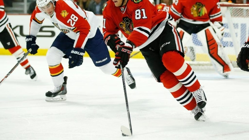 Chicago Blackhawks right wing Marian Hossa (81) advances past Florida Panthers left wing Garrett Wilson (28) during the first period of an NHL hockey game on Tuesday, Feb. 24, 2015, in Chicago. (AP Photo/Andrew A. Nelles)