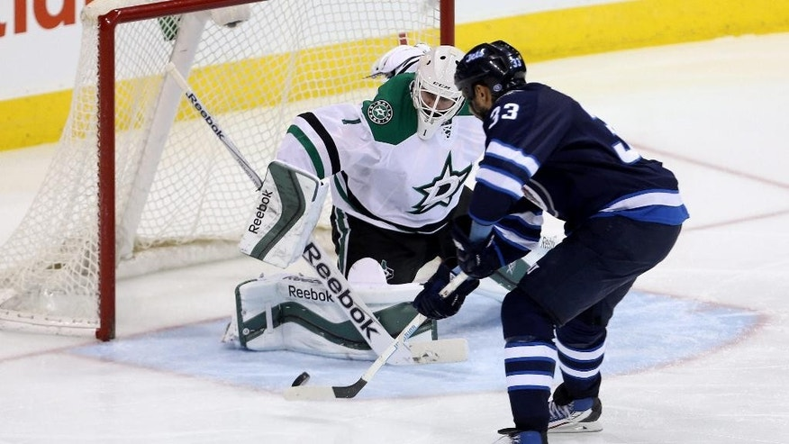 Winnipeg Jets' Dustin Byfuglien (33) scores on Dallas Stars goaltender Jhonas Enroth (1) during the third period of an NHL hockey game Tuesday, Feb. 24, 2015, in Winnipeg, Manitoba. The Jets won 4-2. (AP Photo/The Canadian Press, Trevor Hagan)