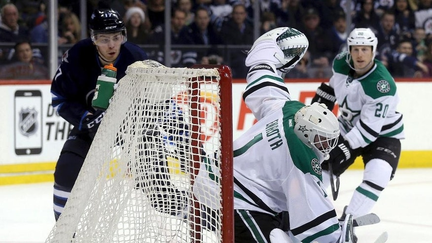 Winnipeg Jets' Adam Lowry (17)  scores on Dallas Stars goaltender Jhonas Enroth (1) as Cody Eakin (20) watches during the second period of an NHL hockey game Tuesday, Feb. 24, 2015, in Winnipeg, Manitoba. (AP Photo/The Canadian Press, Trevor Hagan)