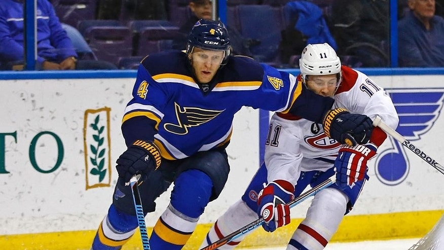 St. Louis Blues' Carl Gunnarsson, left, of Sweden, battles for the puck against Montreal Canadiens' Brendan Gallagher, right, during the first period of an NHL hockey game Tuesday, Feb. 24, 2015, in St. Louis. (AP Photo/Billy Hurst)