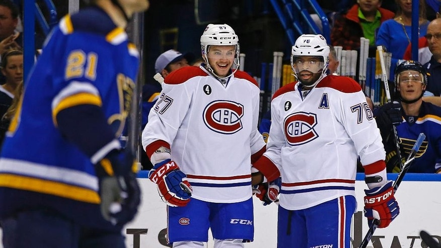 Montreal Canadiens' Alex Galchenyuk, center, is congratulated by teammate P.K. Subban, right, as St. Louis Blues' Patrik Berglund, left, of Sweden, skates back to the bench after Galchenyuk's goal during the first period of an NHL hockey game Tuesday, Feb. 24, 2015, in St. Louis. (AP Photo/Billy Hurst)