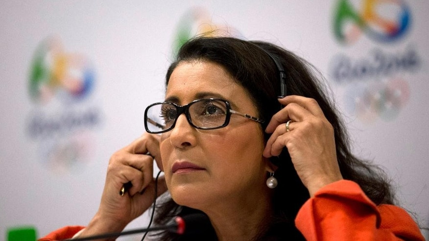 Nawal El Moutawakel, head of the International Olympic Committee's evaluation commission, adjusts her headphone during a press conference in Rio de Janeiro, Brazil, Wednesday, Feb. 25, 2015. IOC inspectors are visiting the Olympic city to check on preparations for the Olympics, just 18 months away. (AP Photo/Silvia Izquierdo)