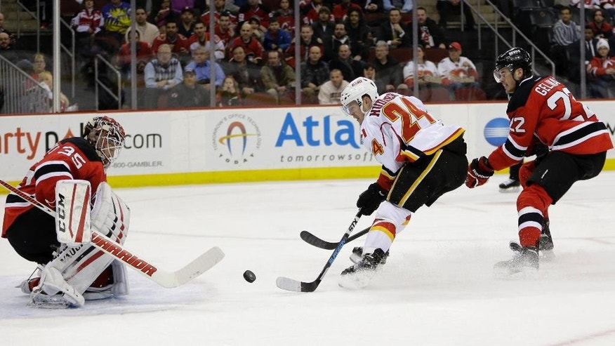 New Jersey Devils goalie Cory Schneider, left, makes a save on a shot by Calgary Flames left wing Jiri Hudler, center, of the Czech Republic, during the first period of an NHL hockey game, Wednesday, Feb. 25, 2015, in Newark, N.J. Devils' Eric Gelinas is at right. (AP Photo/Julio Cortez)