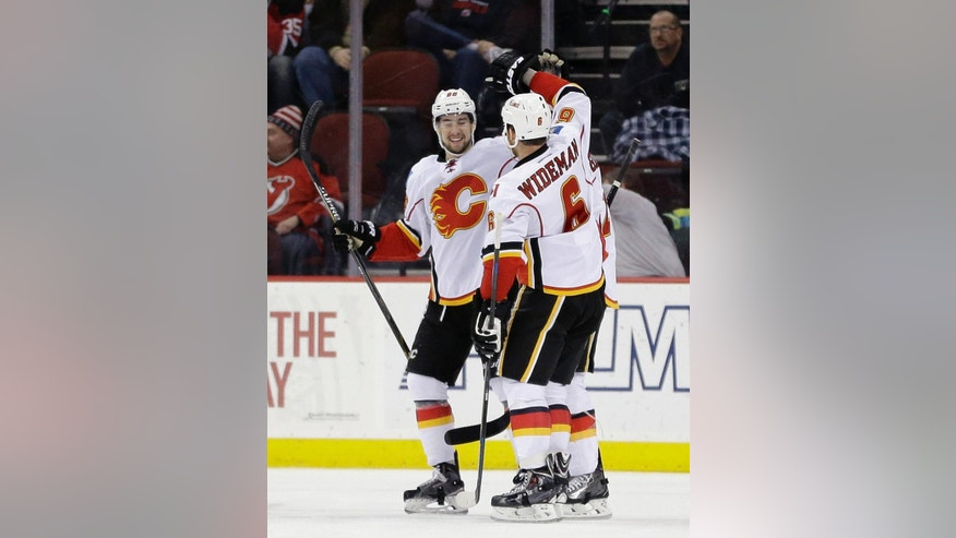 Calgary Flames center Josh Jooris, left, and defenseman Dennis Wideman, right, celebrate after Curtis Glencross, back, scored a goal against the New Jersey Devils during the second period of an NHL hockey game, Wednesday, Feb. 25, 2015, in Newark, N.J. (AP Photo/Julio Cortez)