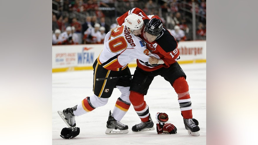 Calgary Flames left wing Curtis Glencross, left, and New Jersey Devils center Travis Zajac fight during the first period of an NHL hockey game, Wednesday, Feb. 25, 2015, in Newark, N.J. (AP Photo/Julio Cortez)