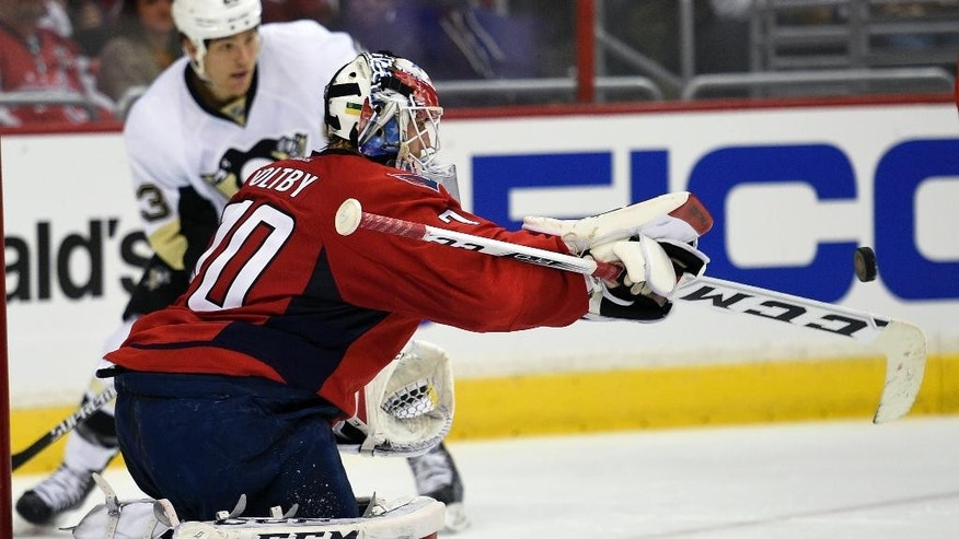 Washington Capitals goalie Braden Holtby (70) reaches for the puck against the Pittsburgh Penguins during the second period of an NHL hockey game, Wednesday, Feb. 25, 2015, in Washington. (AP Photo/Nick Wass)