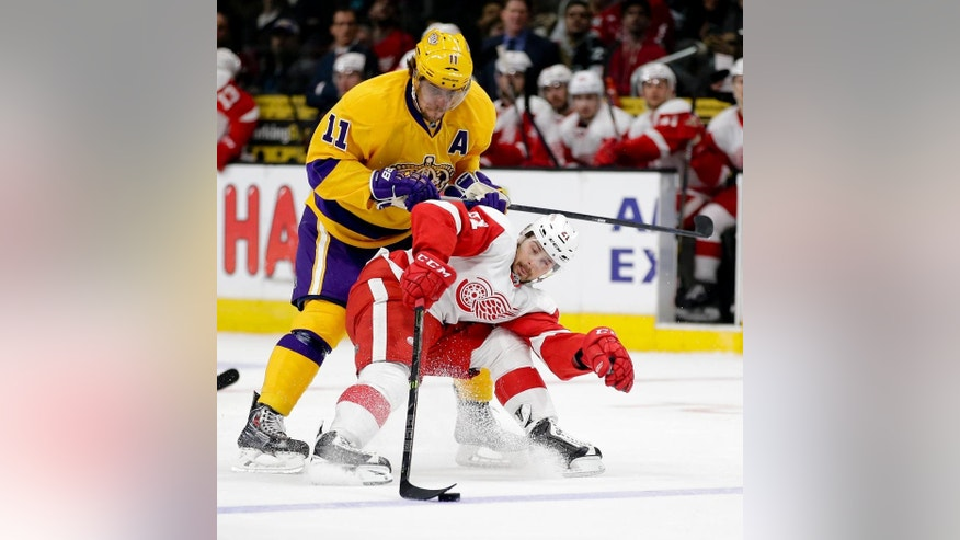 Los Angeles Kings center Anze Kopitar (11) tries to push Detroit Red Wings left wing Tomas Tatar off the puck during the first period of an NHL hockey game in Los Angeles, Tuesday, Feb. 24, 2015. (AP Photo/Chris Carlson)