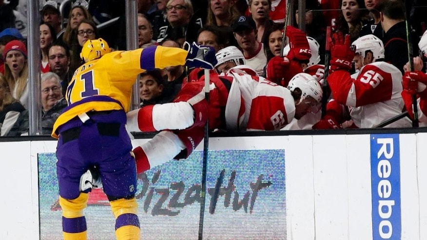Los Angeles Kings center Jordan Nolan, left, knocks Detroit Red Wings defenseman Danny DeKeyser into the bench during the first period of an NHL hockey game in Los Angeles, Tuesday, Feb. 24, 2015. (AP Photo/Chris Carlson)