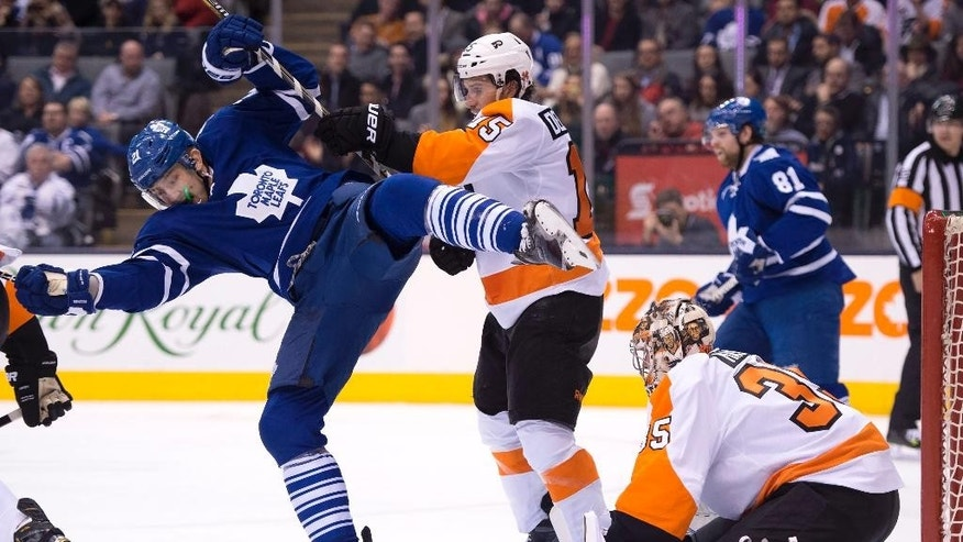 Toronto Maple Leafs James van Riemsdyk (21) gets dumped by Philadelphia Flyers defenceman Michael Del Zotto (15) in front of goaltender Steve Mason during second period of an NHL hockey game in Toronto, Thursday, Feb. 26, 2015. (AP Photo/The Canadian Press, Frank Gunn)