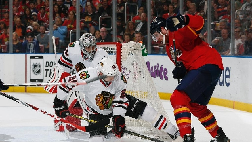 Chicago Blackhawks goaltender Corey Crawford (50) looks on as defenseman Kyle Cumiskey (26) helps defend the shot by Florida Panthers forward Jimmy Hayes (12) during the second period of an NHL hockey game, Thursday, Feb. 26, 2015, in Sunrise, Fla. (AP Photo/Joel Auerbach)