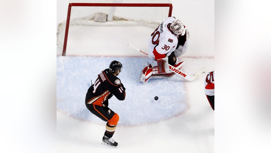 Ottawa Senators goalie Andrew Hammond, right, blocks a shot by Anaheim Ducks left wing Rene Bourque during the first period of an NHL hockey game in Anaheim, Calif., Wednesday, Feb. 25, 2015. (AP Photo/Chris Carlson)