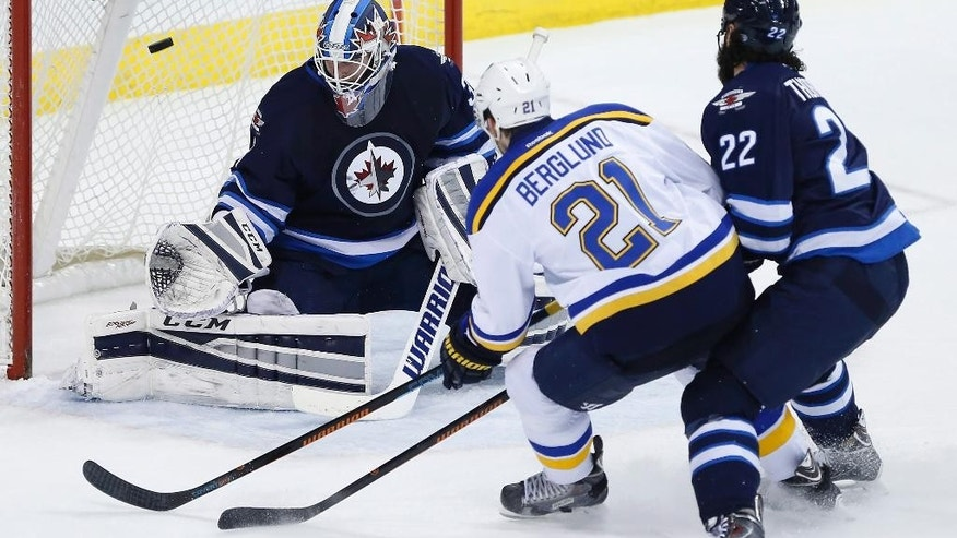 St. Louis Blues' Patrik Berglund (21) scores on Winnipeg Jets goaltender Michael Hutchinson (34) as Chris Thorburn (22) defends during the second period of an NHL hockey game Thursday, Feb. 26, 2015, in Winnipeg, Manitoba. (AP Photo/The Canadian Press, John Woods)