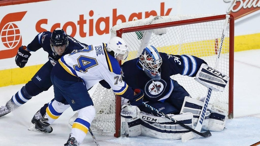 St. Louis Blues' T.J. Oshie (74) misses on the wraparound on Winnipeg Jets goaltender Michael Hutchinson (34) as Tyler Myers (57) defends during the second period of an NHL hockey game Thursday, Feb. 26, 2015, in Winnipeg, Manitoba. (AP Photo/The Canadian Press, John Woods)
