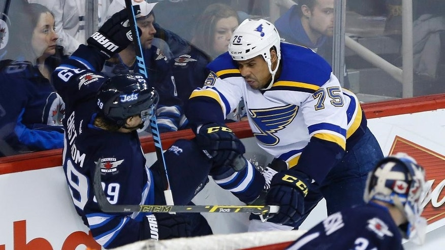 Winnipeg Jets' Toby Enstrom (39) gets checked by St. Louis Blues' Ryan Reaves (75) as Jets goaltender Michael Hutchinson (34) watches during the second period of an NHL hockey game Thursday, Feb. 26, 2015, in Winnipeg, Manitoba. (AP Photo/The Canadian Press, John Woods)