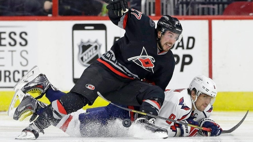 Carolina Hurricanes' Justin Faulk, top, and Washington Capitals' Alex Ovechkin (8), of Russia, fall to the ice chasing the puck during the second period of an NHL hockey game in Raleigh, N.C., Friday, Feb. 27, 2015. (AP Photo/Gerry Broome)