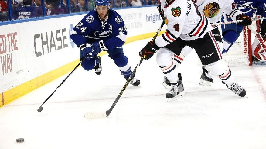 Tampa Bay Lightning right wing Ryan Callahan (24) and Chicago Blackhawks defenseman Niklas Hjalmarsson (4), of Sweden, advance on the puck during the second period of an NHL hockey game Friday, Feb. 27, 2015, in Tampa, Fla. (AP Photo/Brian Blanco)