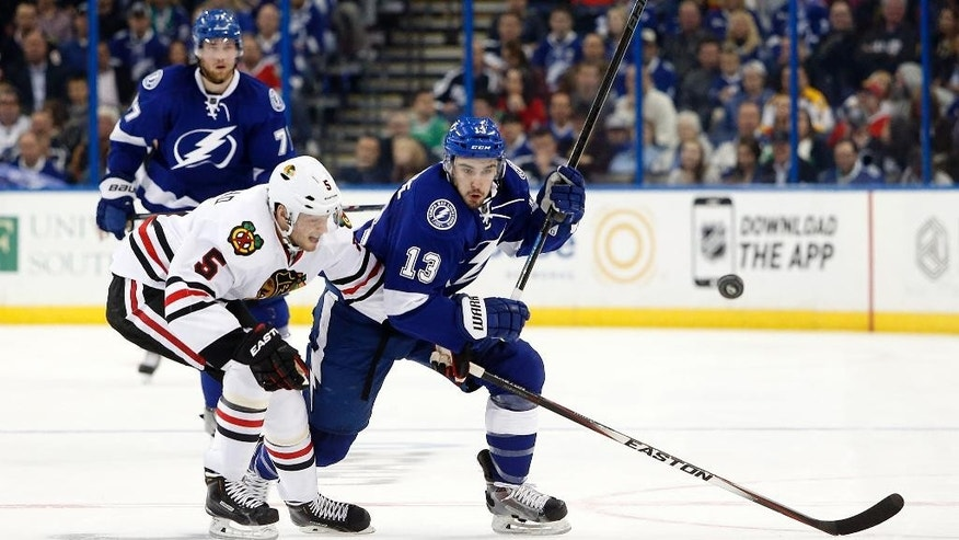 Tampa Bay Lightning center Cedric Paquette (13) and Chicago Blackhawks defenseman David Rundblad (5), of Sweden, battle for the pucks during the second period of an NHL hockey game Friday, Feb. 27, 2015, in Tampa, Fla. (AP Photo/Brian Blanco)
