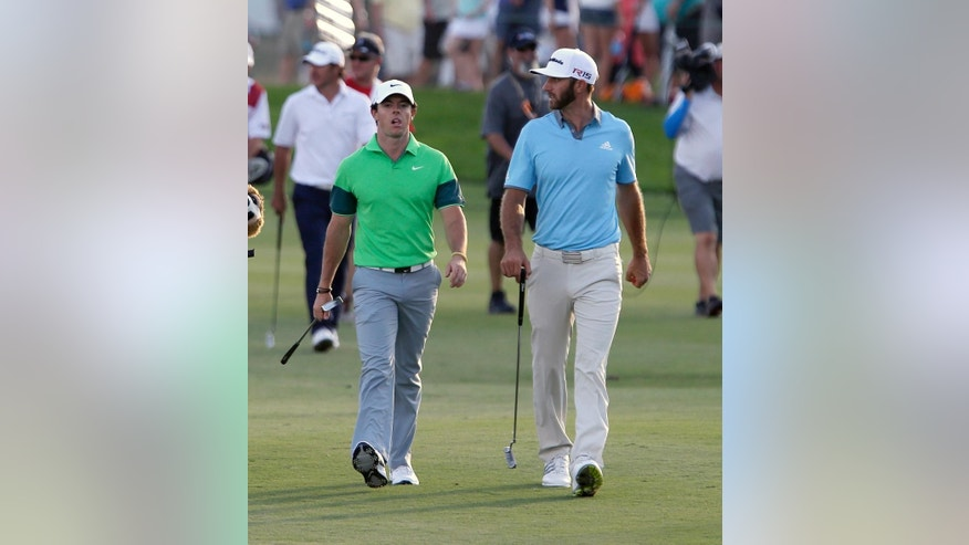 Rory McIlroy, of Northern Ireland, left, and Dustin Johnson, right, talk to each other on the fairway as they approach the 18th hole during the first round of the Honda Classic golf tournament Thursday, Feb. 26, 2015, in Palm Beach Gardens, Fla. (AP Photo/Alan Diaz)