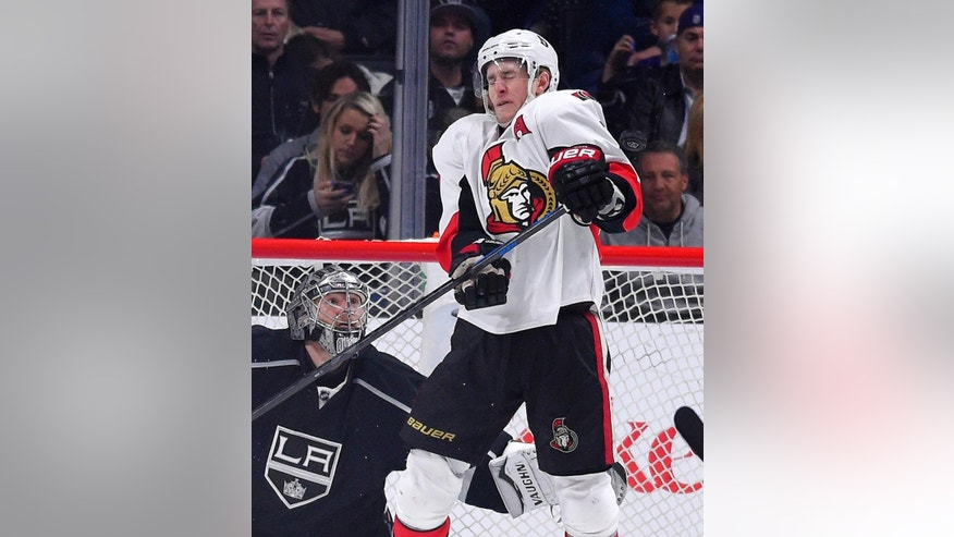 Ottawa Senators center Kyle Turris, right, is struck and injured by the puck as Los Angeles Kings goalie Jonathan Quick watches during the second period of an NHL hockey game, Thursday, Feb. 26, 2015, in Los Angeles. (AP Photo/Mark J. Terrill)