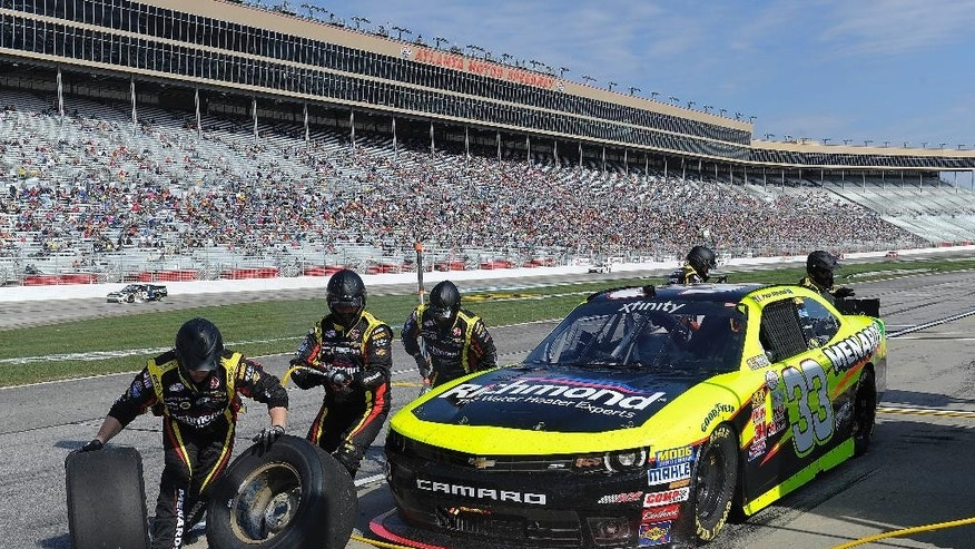 Pit crew members work on Paul Menard's car during a pit stop in the NASCAR Xfinity series auto race at Atlanta Motor Speedway Saturday, Feb. 28, 2015, in Hampton, Ga.  (AP Photo/John Amis)